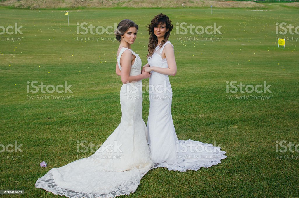 Two beautiful brides holding hands on the green field stock photo