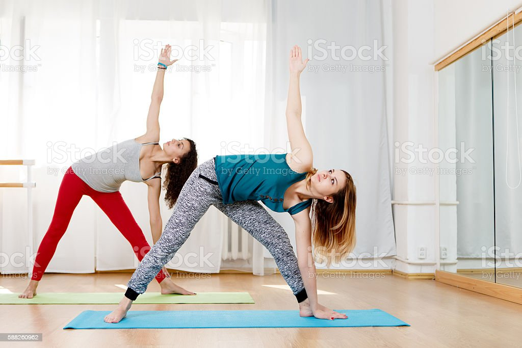 Two beautiful flexible women practices yoga asana extended triangle stock photo