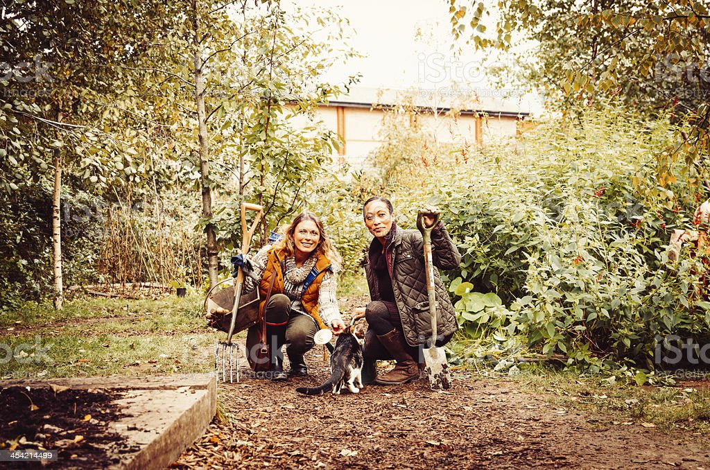 Two Beautiful Gardeners With A Cat In The Garden stock photo