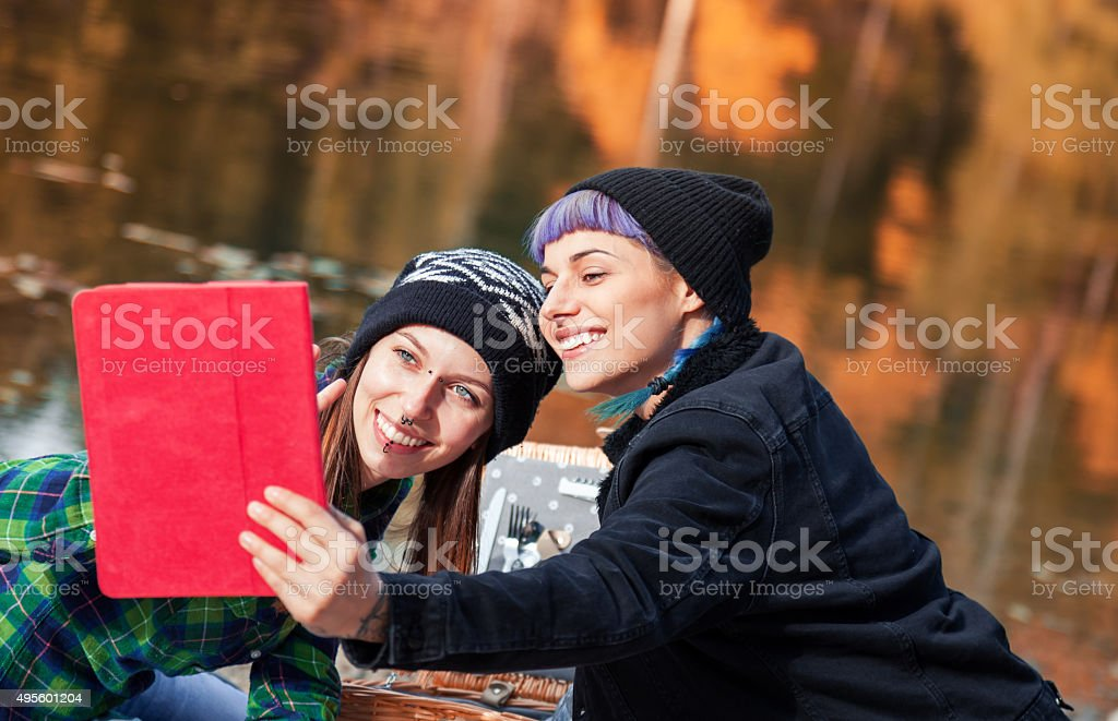 Two beautiful girl, play with tablet stock photo