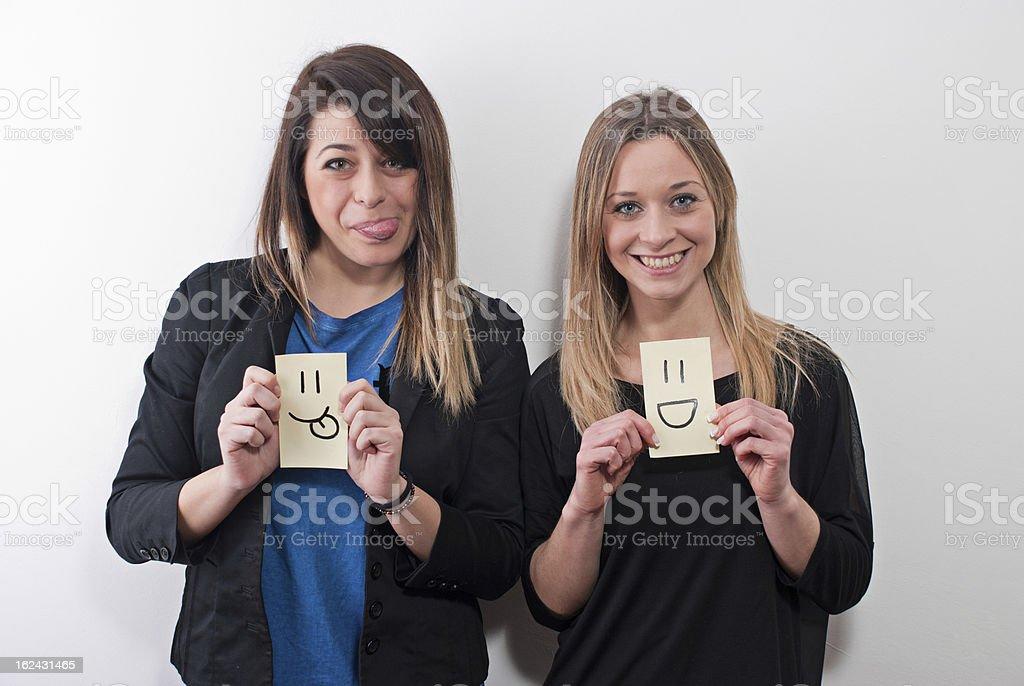 Two beautiful girls having fun with post-it. stock photo