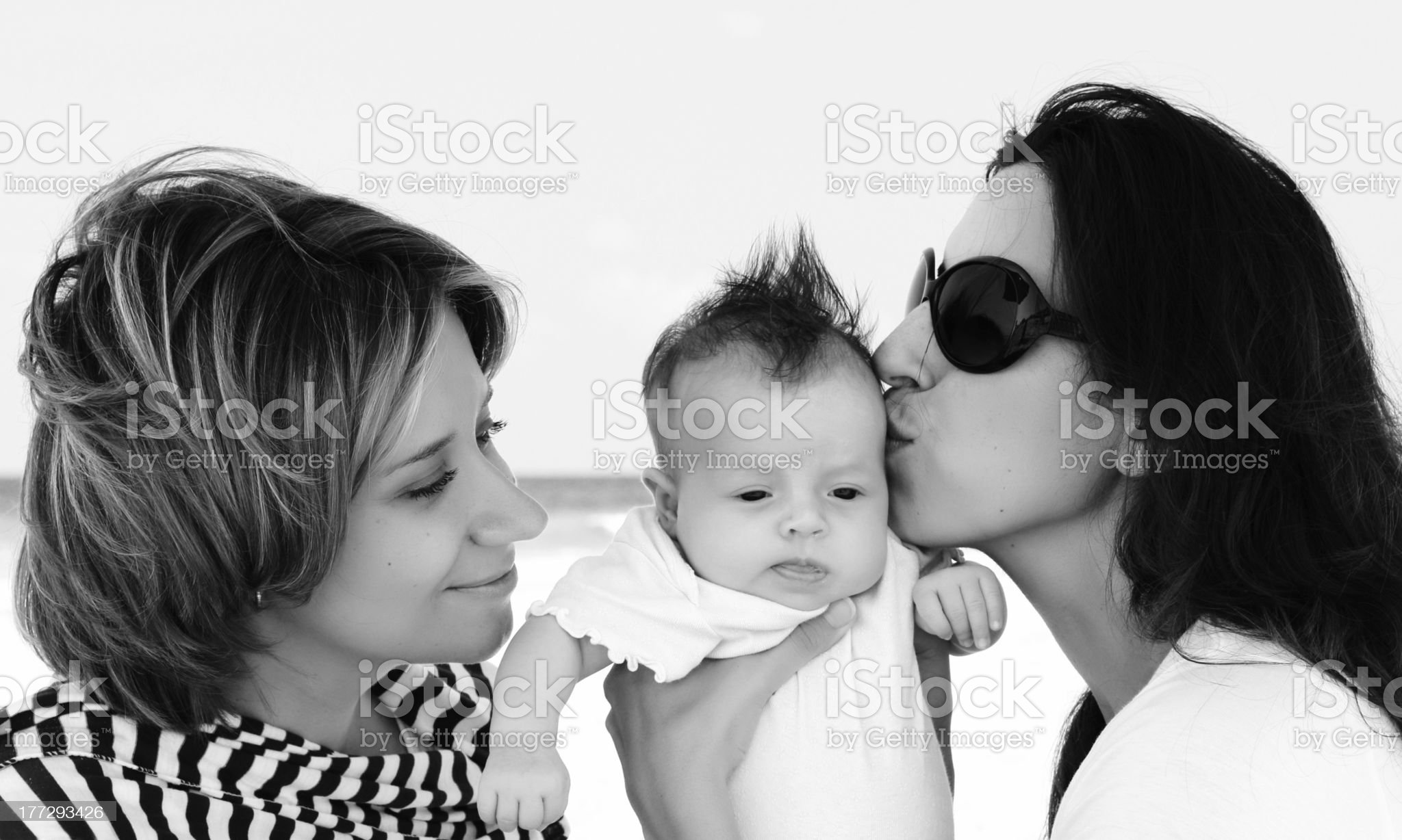 two beautiful girls with a baby on the beach royalty-free stock photo