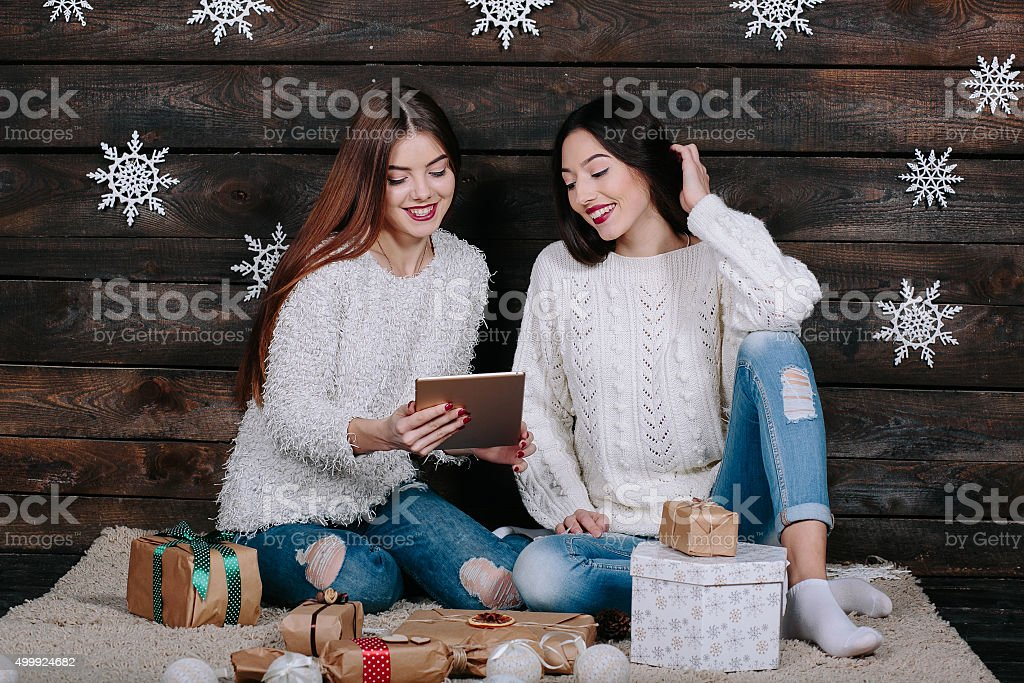 Two beautiful girls with a tablet, between gifts stock photo