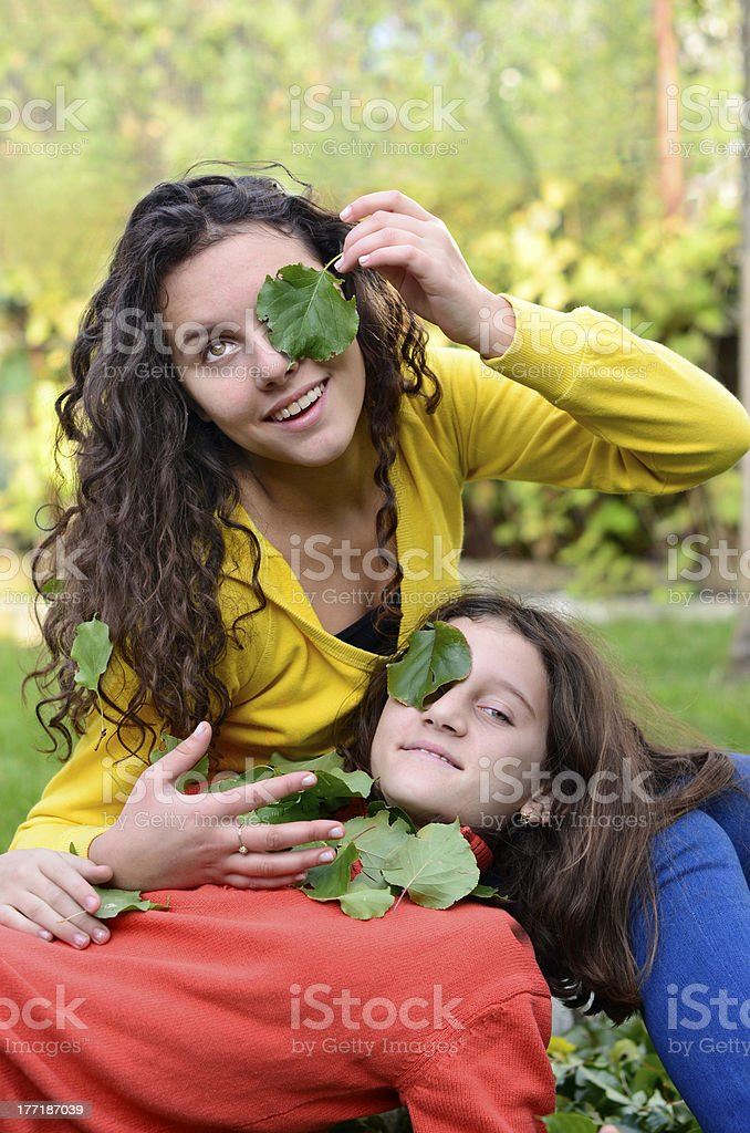 two beautiful  happy kids playing with leafs in garden stock photo