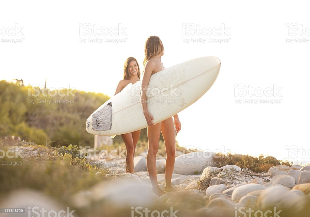 Two beautiful healthy young women going for a surf together royalty-free stock photo