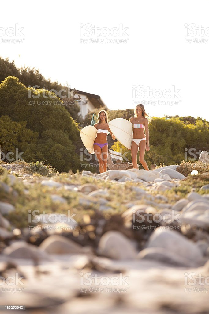 Two beautiful healthy young women going for a surf together stock photo