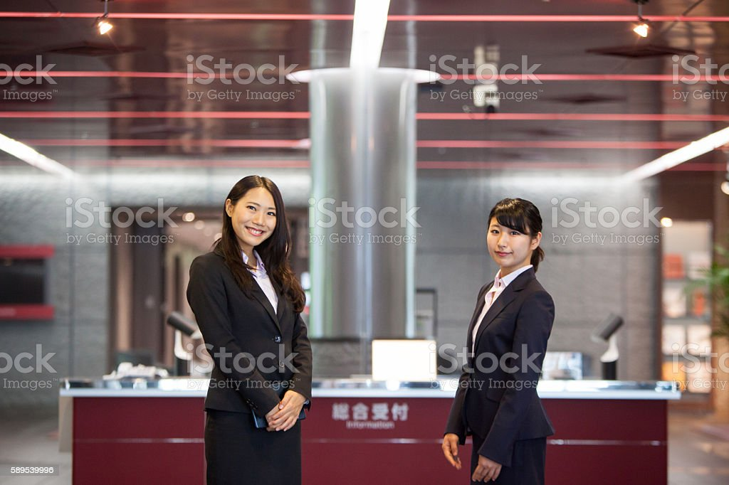 Two Beautiful Japanese women await at reception desk stock photo