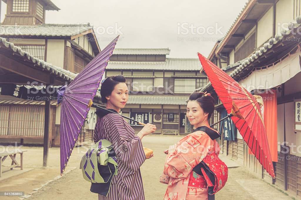Two Beautiful Japanese Women in Kimono Holding Parasols Smiling, Kyoto stock photo