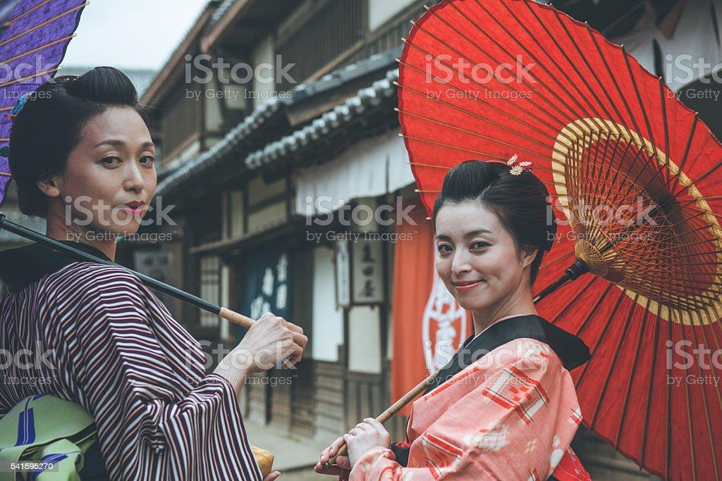 Two Beautiful Japanese Women in Kimono, with Parasols, Smiling, Kyoto stock photo