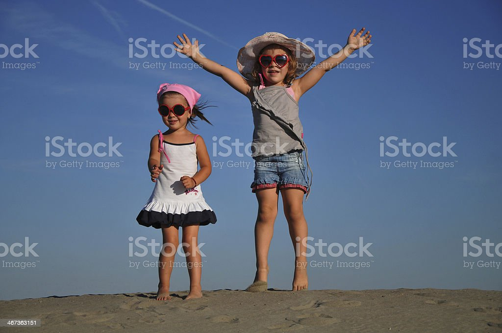 Two beautiful little girls jumping on the sand stock photo