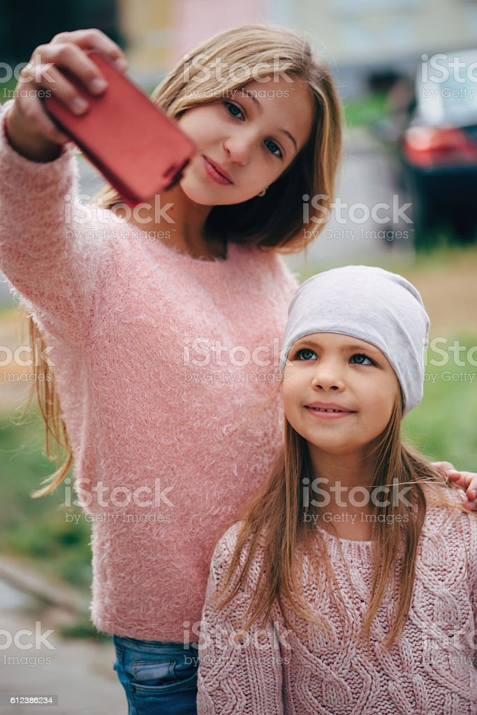 two beautiful little girls making selfie stock photo