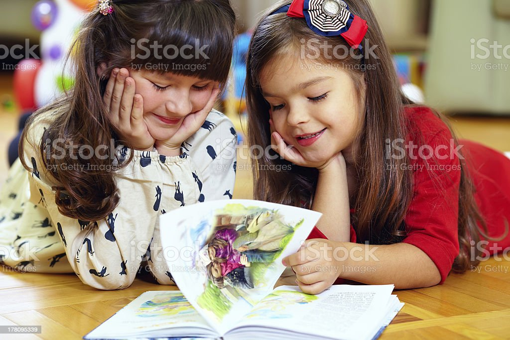 two beautiful little girls reading book at home stock photo