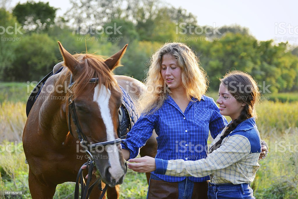 Two Beautiful Smiling Cowgirls with horse royalty-free stock photo