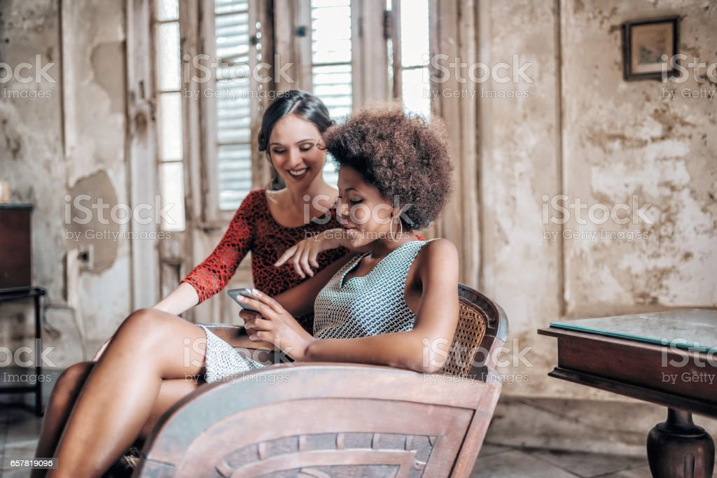 two beautiful stylish young cuban woman looking at mobile indoors stock photo