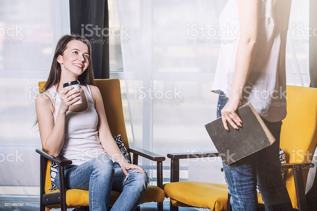 Two beautiful women friends talking happy smiles at home stock photo