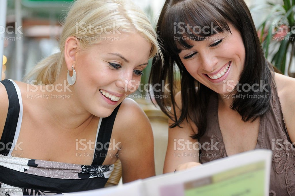 Two beautiful women outdoor looking at the menu royalty-free stock photo