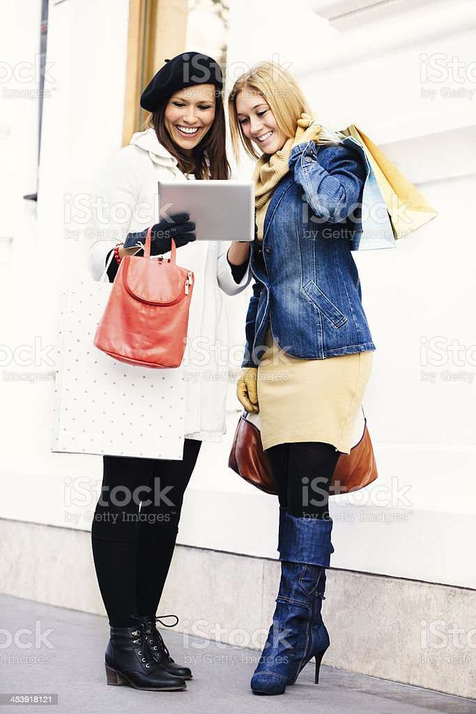 Two beautiful women posing with shopping bags royalty-free stock photo
