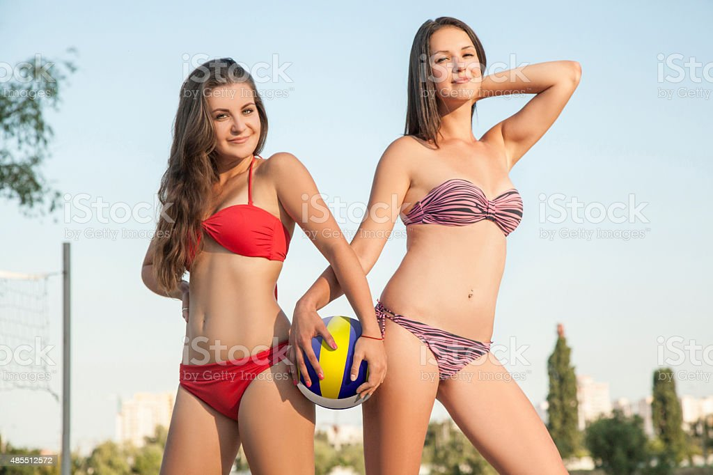 Two beautiful young girl are holding volleyball ball and smiling stock photo