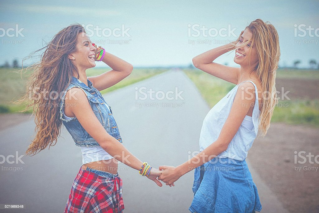 Two beautiful, young smiling women holding hands and sharing moment stock photo