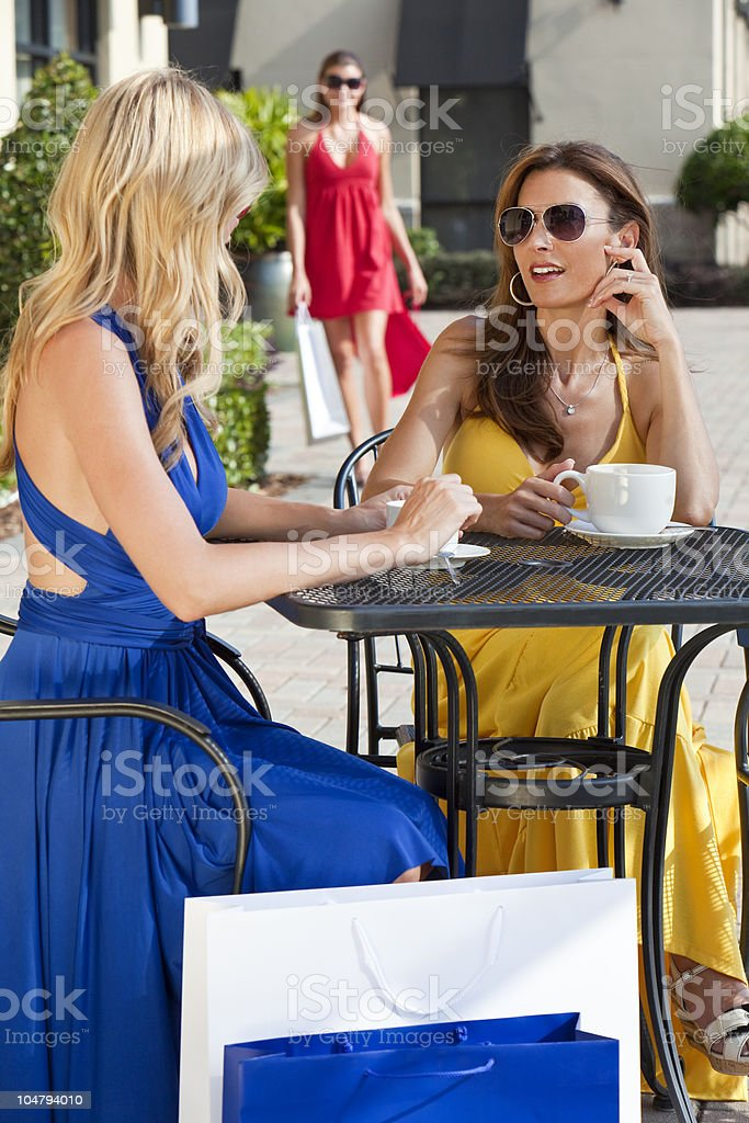 Two Beautiful Young Women Having Coffee With Shopping Bags royalty-free stock photo