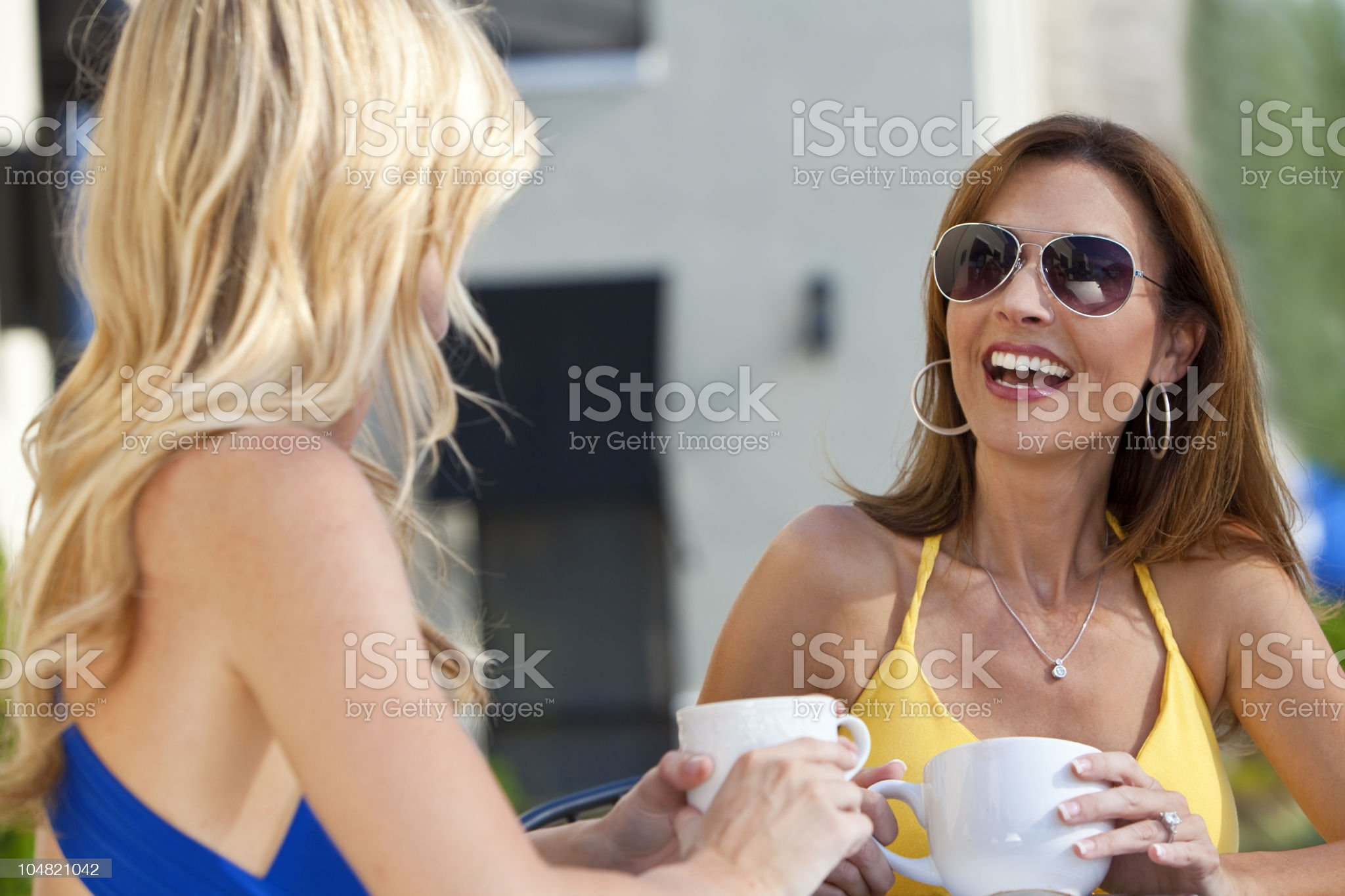 Two Beautiful Young Women Laughing and Drinking Coffee royalty-free stock photo