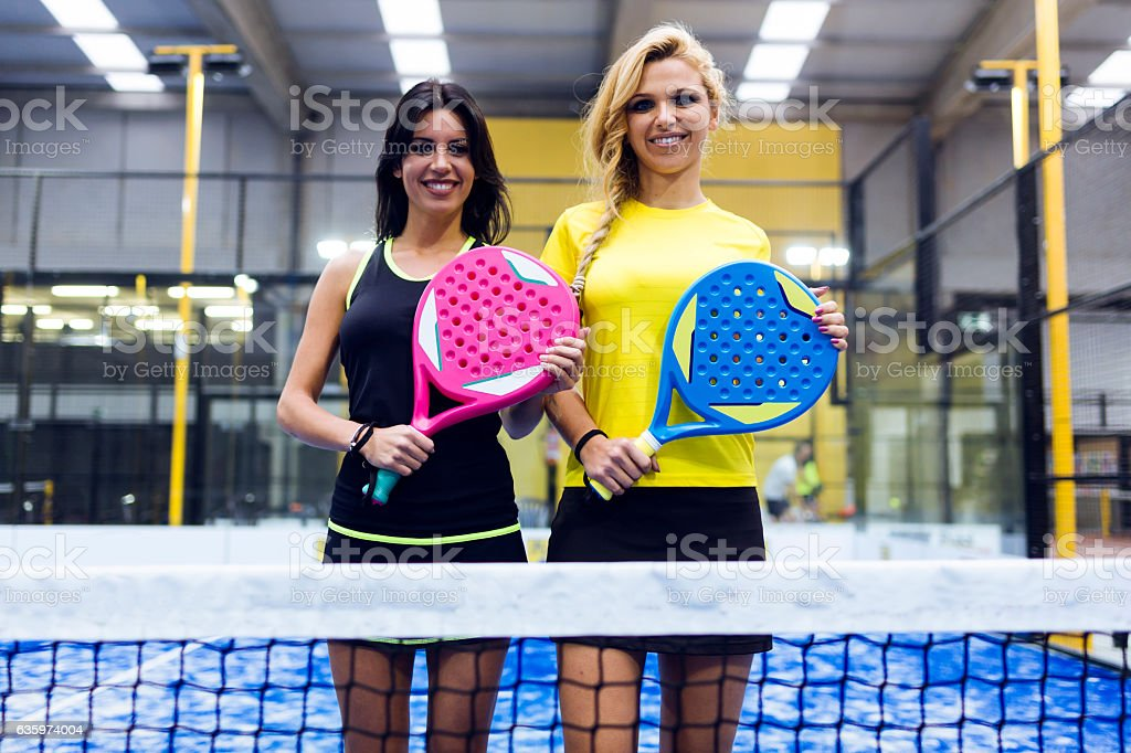 Two beautiful young women posing on paddle tennis court. stock photo