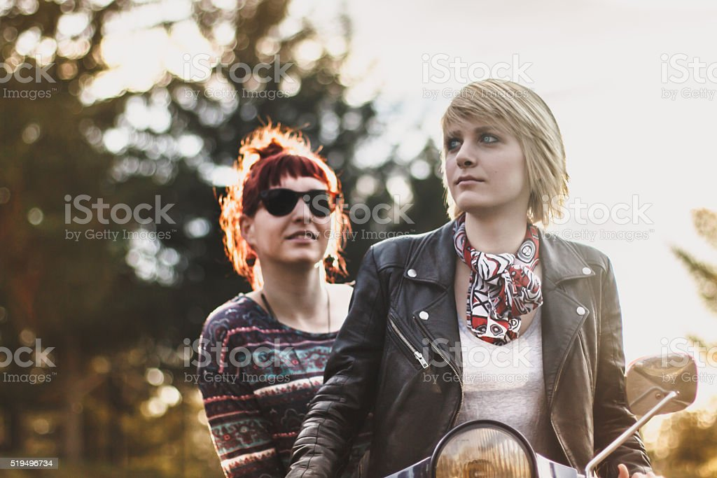 Two beautiful young women riding motorcycle and posing in nature stock photo