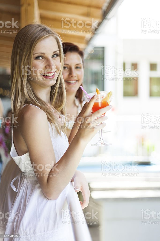 Two Beautiful Young Women Smiling At Camera While Holding Cocktails royalty-free stock photo