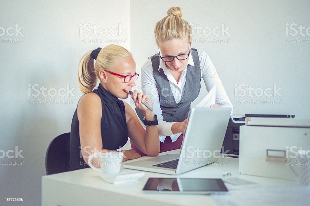 Two beautiful young women working from home office stock photo