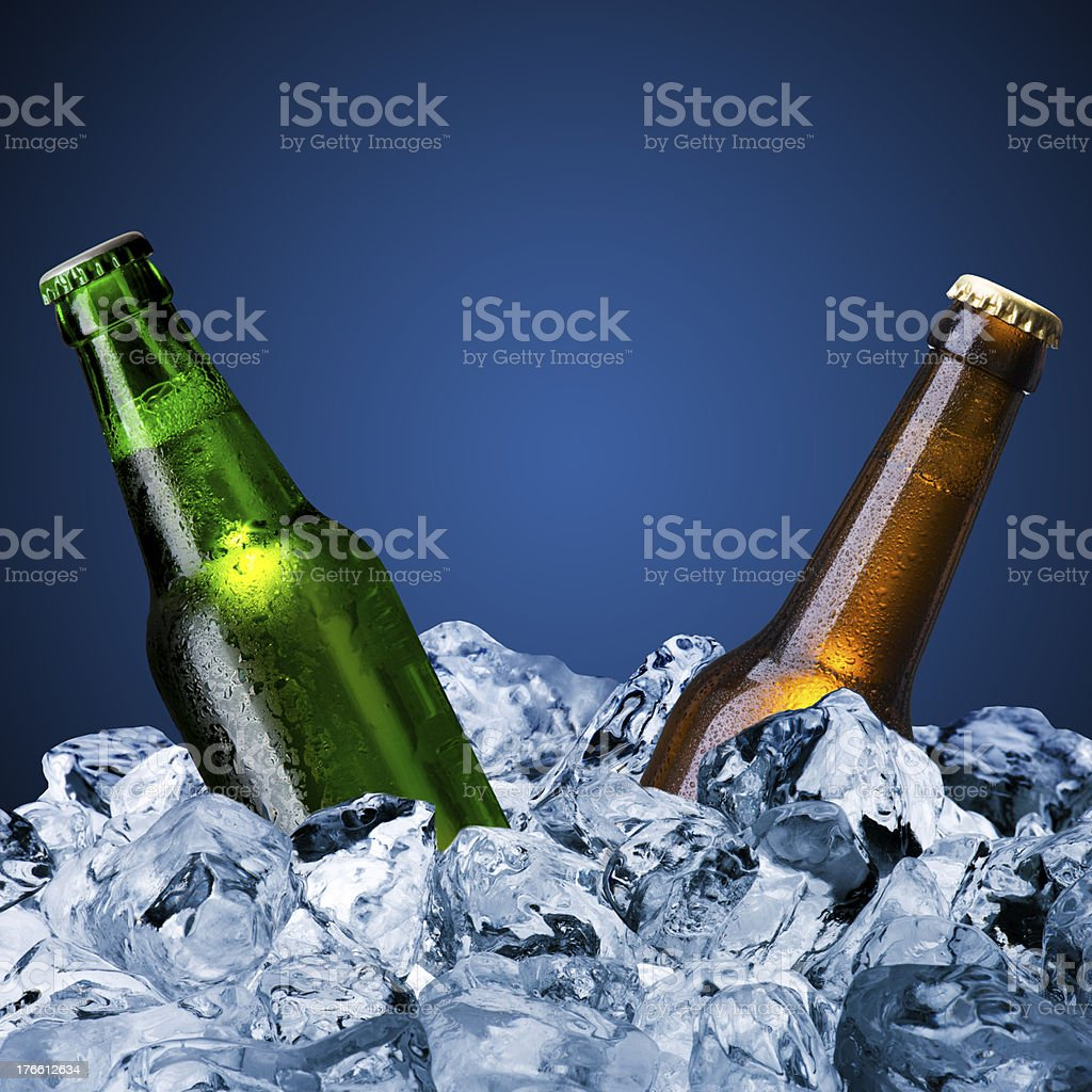 Two beer bottles amongst ice cubes stock photo