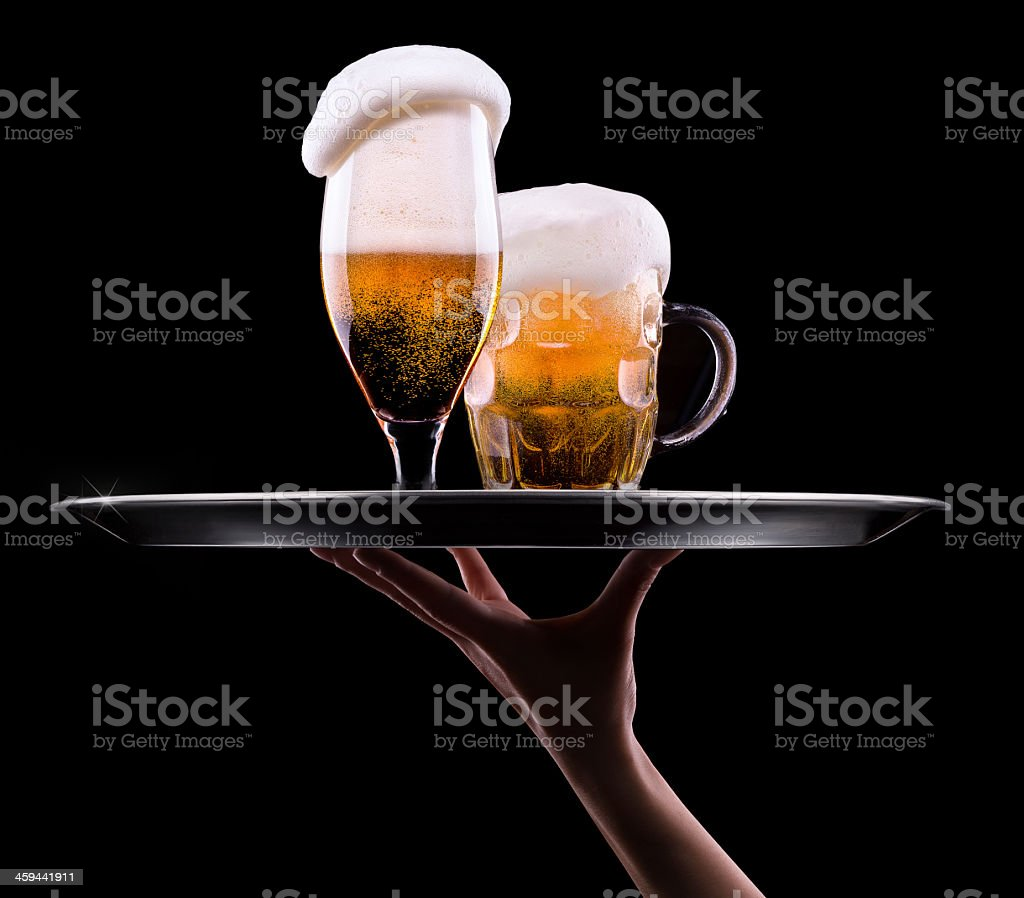 Two beer glasses with foam on a waiter tray stock photo