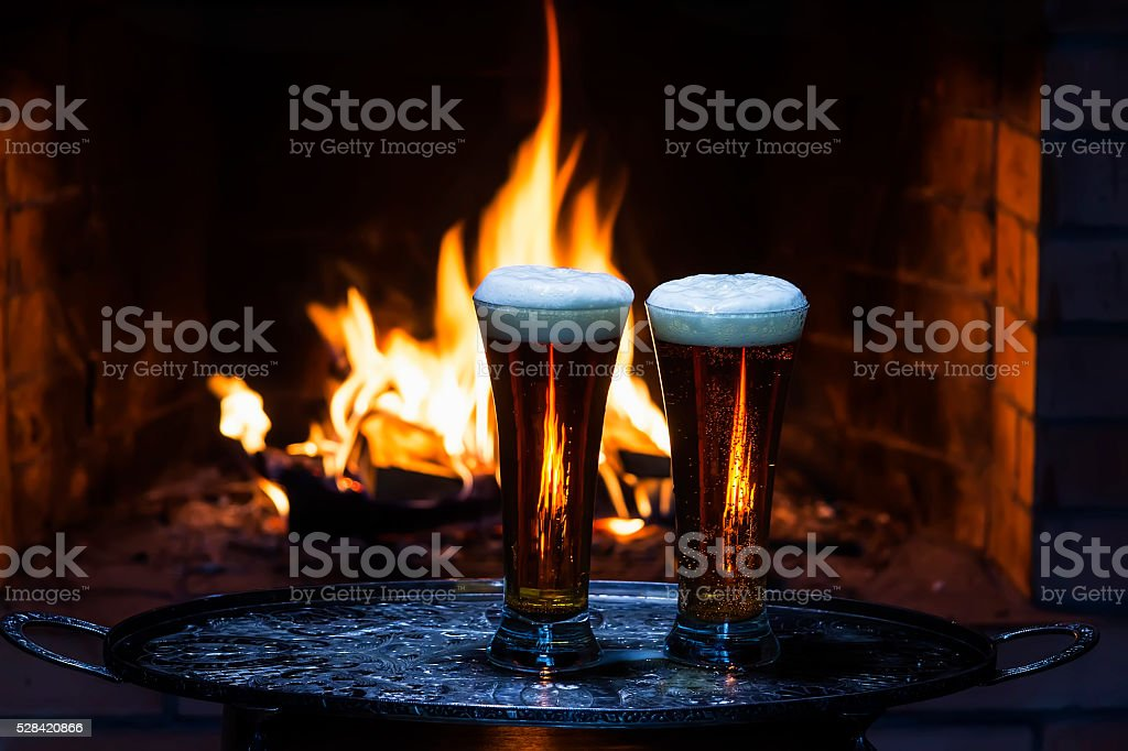 two beers with fireplace on background stock photo