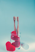 Two beige dental brushes with red hearts Love. Valentine day.