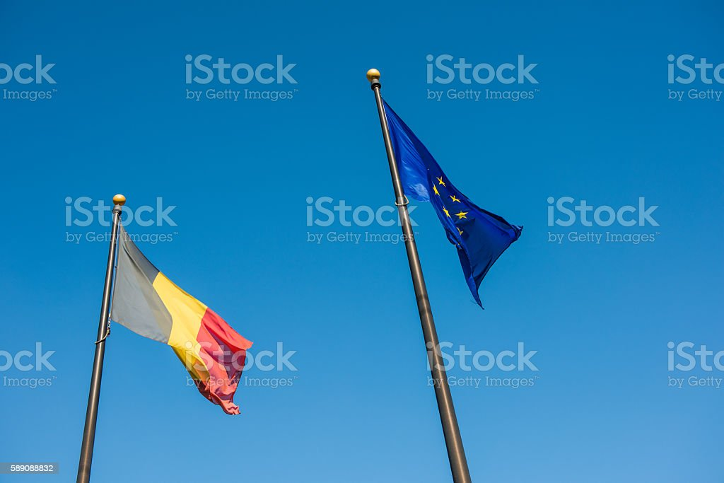 Two Belgian and European Union flags against blue sky stock photo