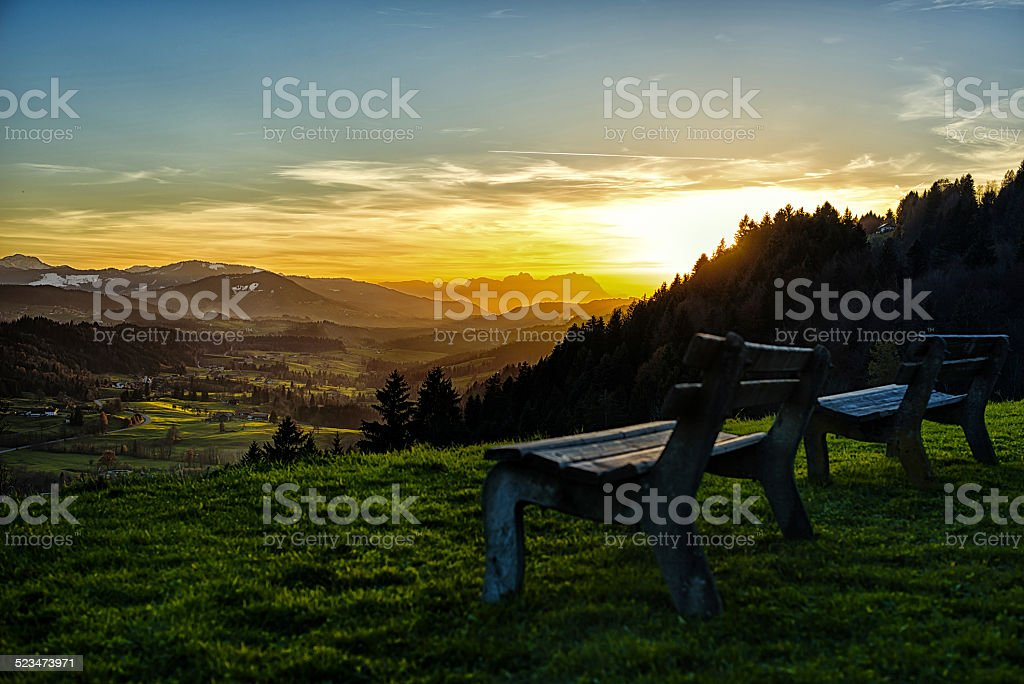 two benches and spectacular sunset over European alps landscape stock photo