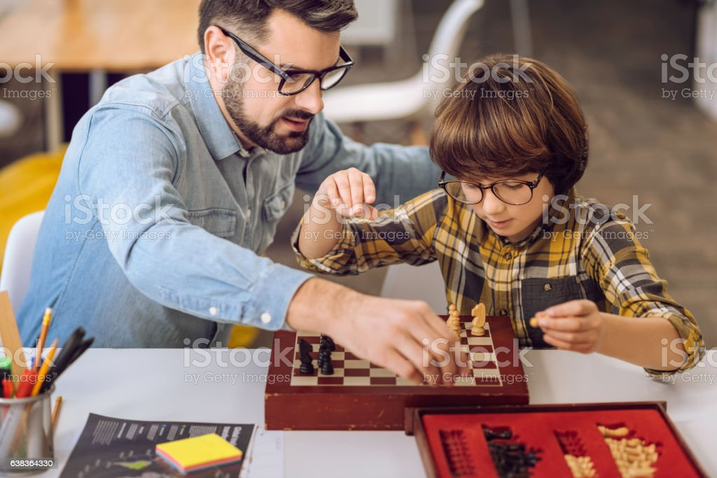 Two best friends laying chess on the desk stock photo