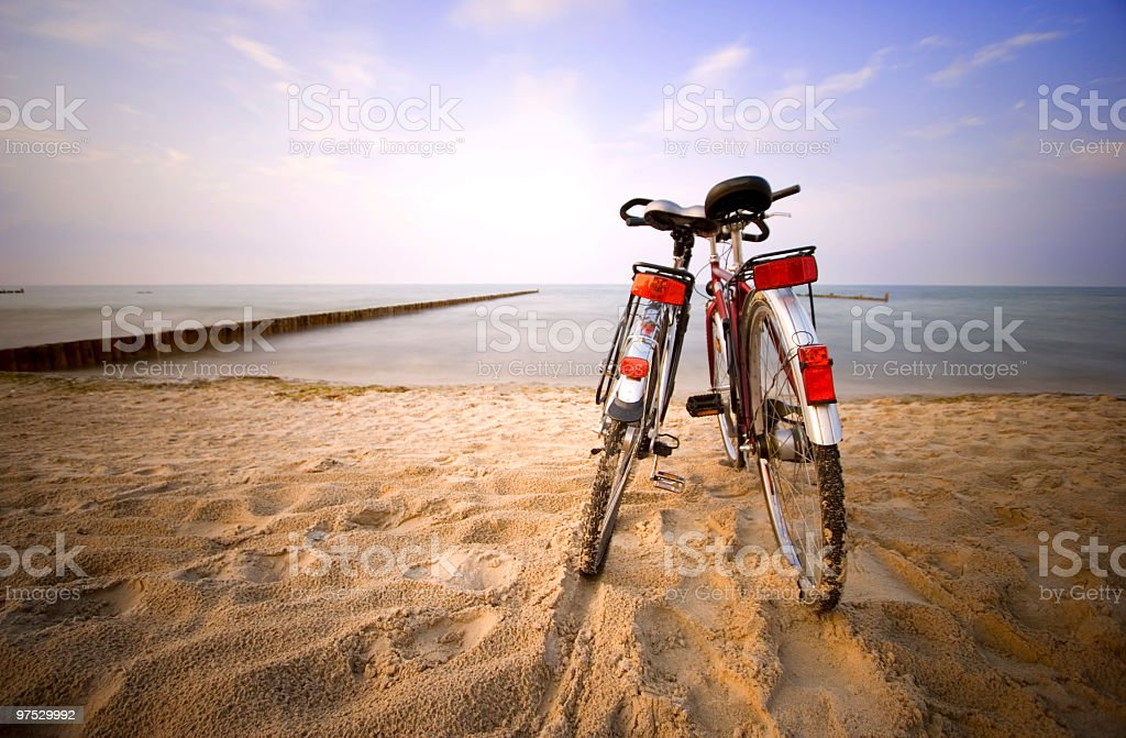 Two bicycles in a romantic pose on a sandy beach stock photo