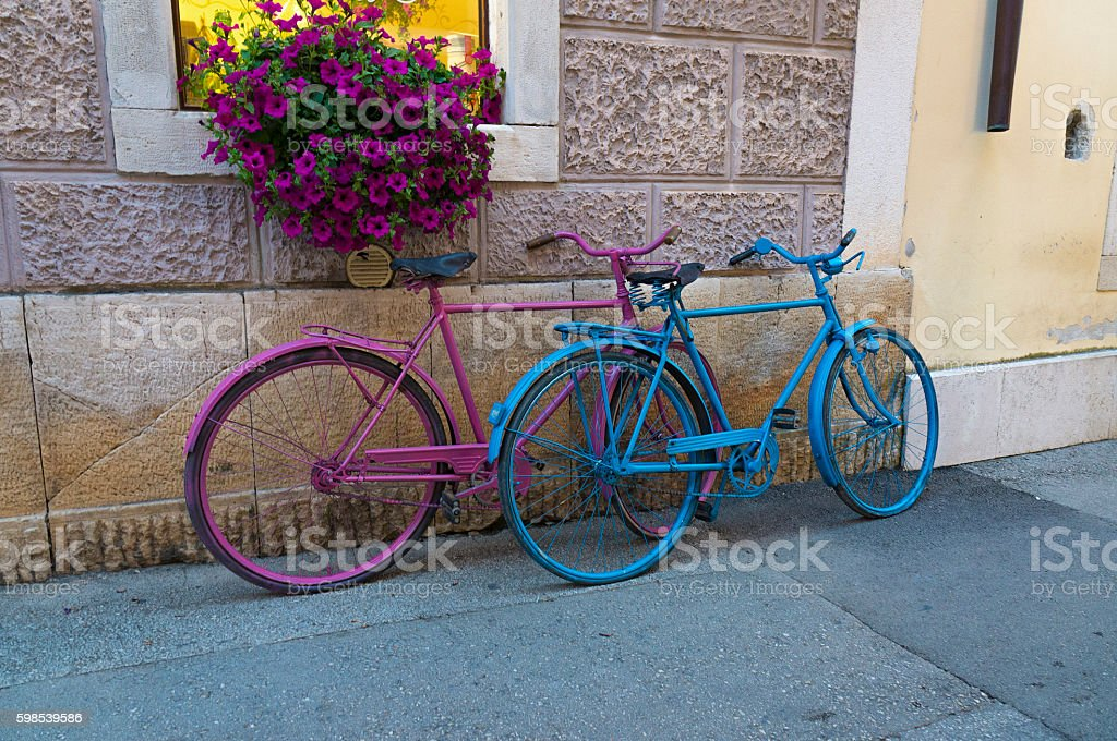 Two bicycles pink and blue against the wall stock photo