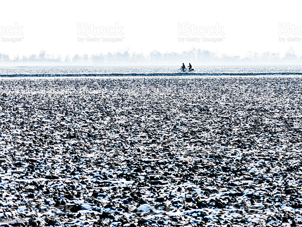 Two bicyclists in polder in winter, Holland stock photo
