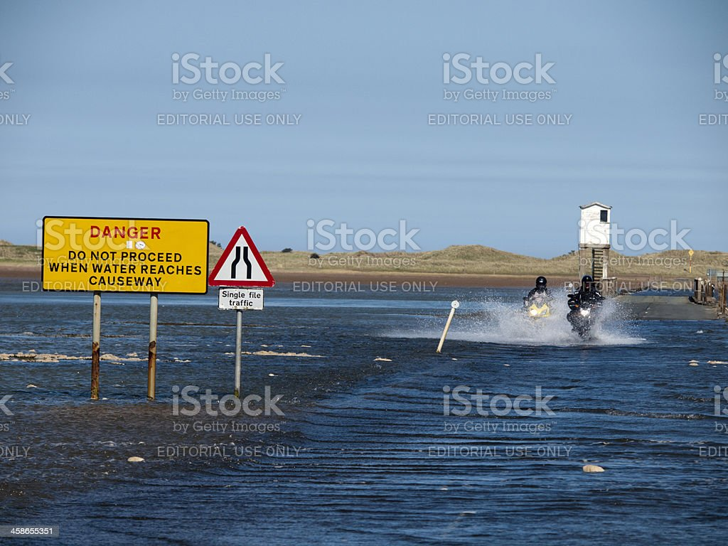 Two bikers crossing the causeway to Holy Island stock photo
