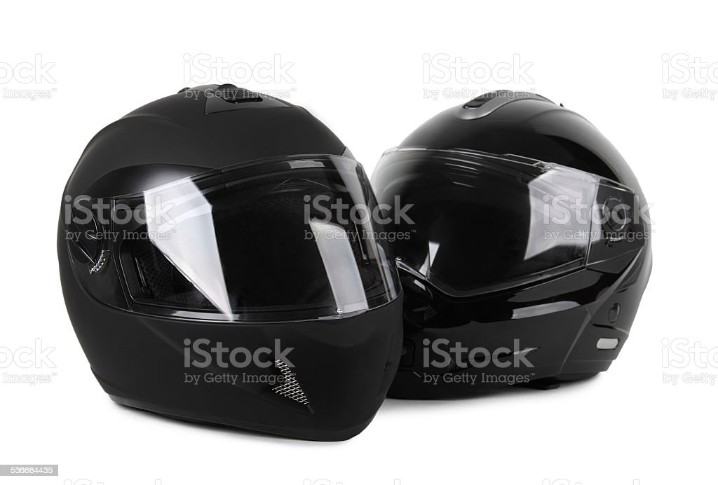 two black motorcycle helmets isolated stock photo