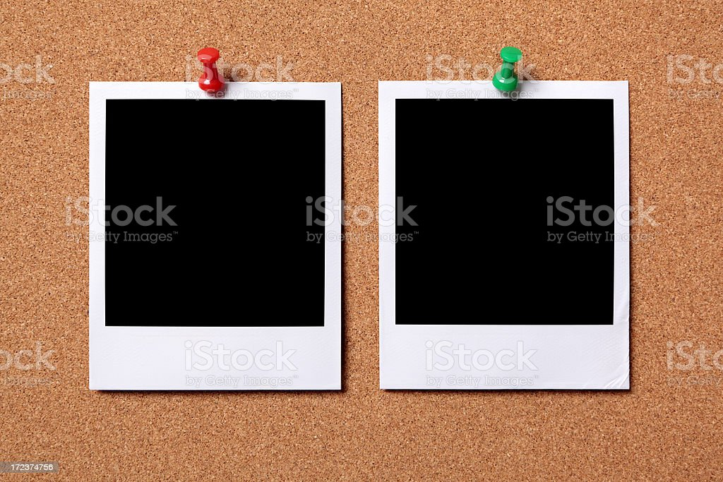 Two blank photos pinned to a cork board royalty-free stock photo