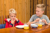 Two blond boys enjoying breakfast outdoors.