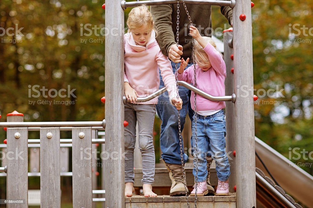 Two blonde sister children playing together in autumnal park surroundings stock photo