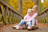 Two blonde sister children posing together in autumnal park surroundings