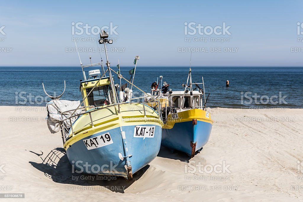 Two blue and yellow fishing boats on the sand. stock photo
