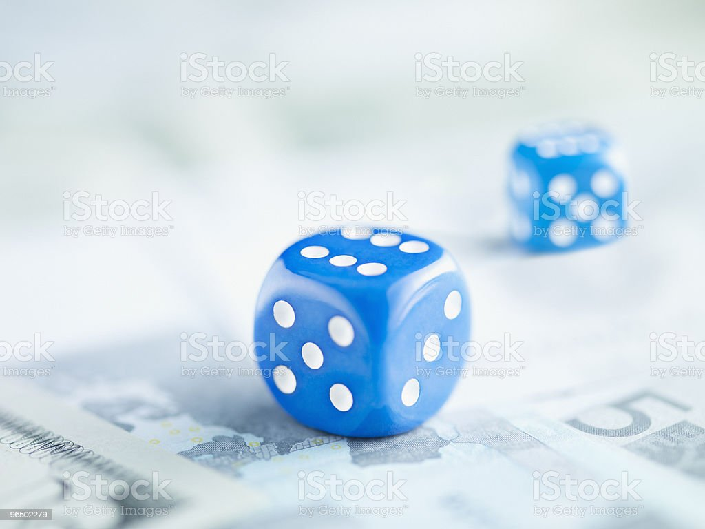 Two blue dice on pile of euro notes stock photo