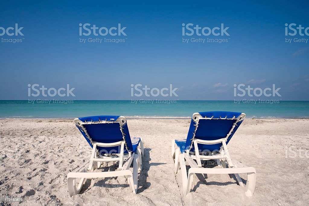 Two blue empty beach chairs on white sand facing the ocean stock photo