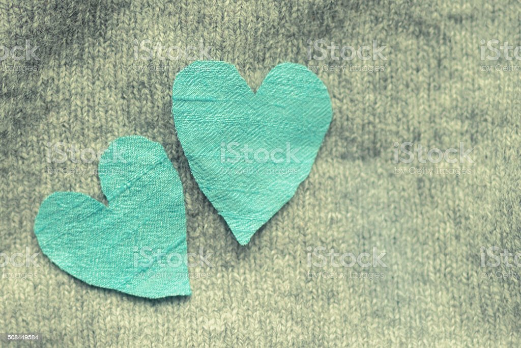 Two blue silk hearts arranged on grey knit stock photo
