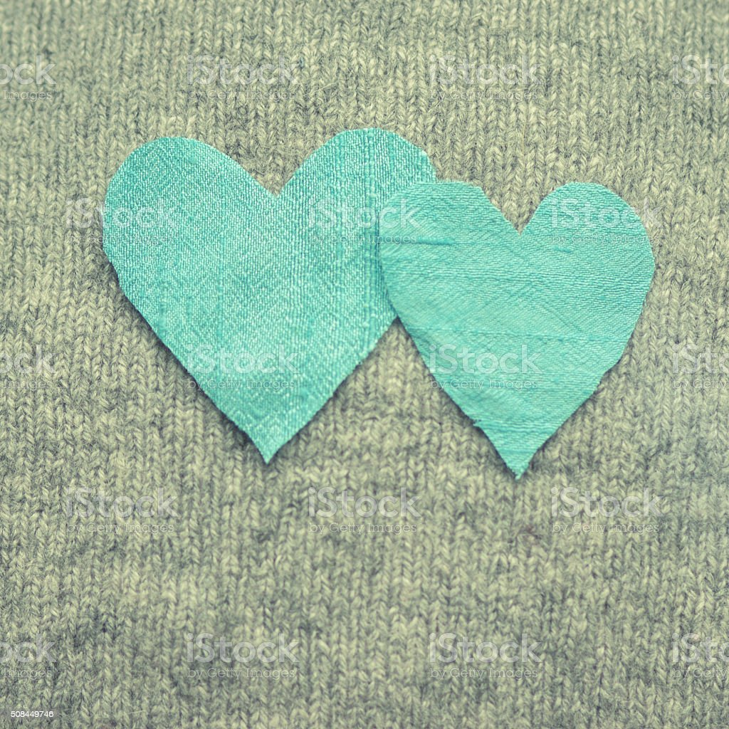 Two blue silk hearts side by side on grey knit stock photo